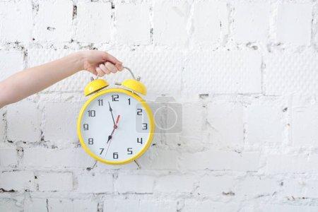 Photo pour Femme main tenant réveil contre mur blanc en brique vierge - image libre de droit