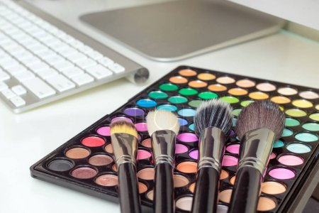 Makeup brushes on colorful makeup palette