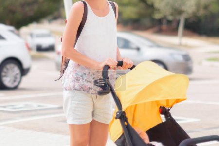 Young woman with a stroller on the city street