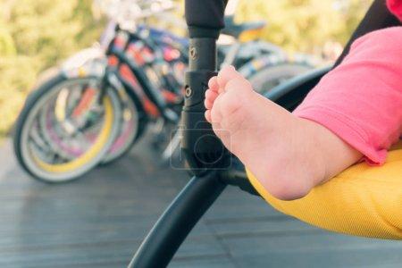 Baby barefoot in stroller outdoor