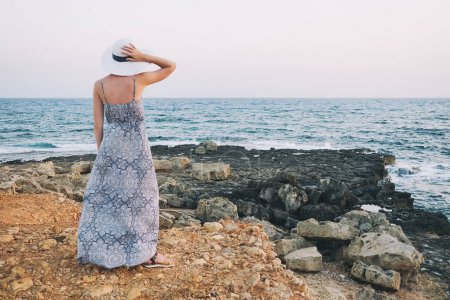 Young woman in hat looking at sea