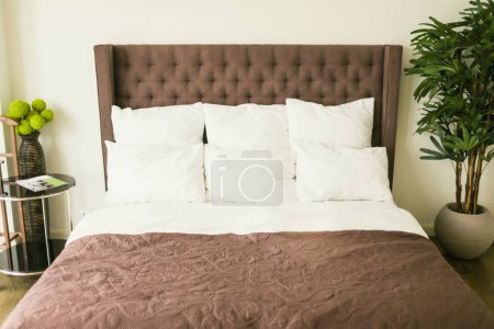 Bed with pillows with bedside table