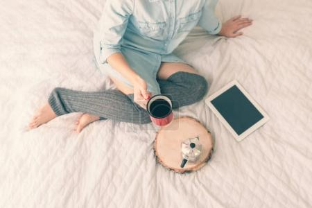 Woman with coffee sitting on bed