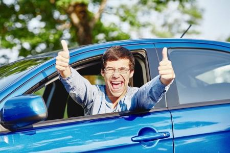 Guy inside car showing thumbs up