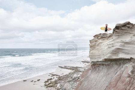 Surfer girl on cliff near ocean