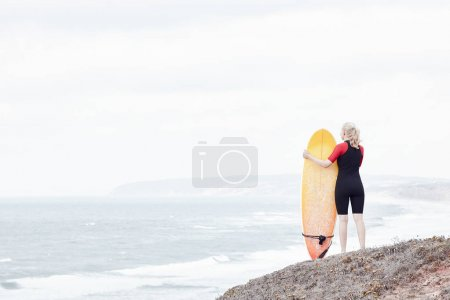 Surfer girl near ocean