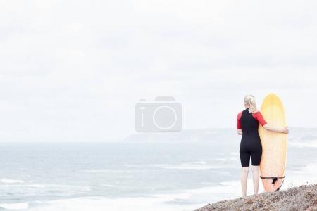 Surfer girl near ocean