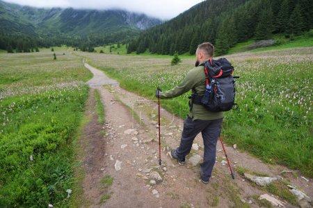 voyageur avec sac à dos suit la route. Paysage de montagne