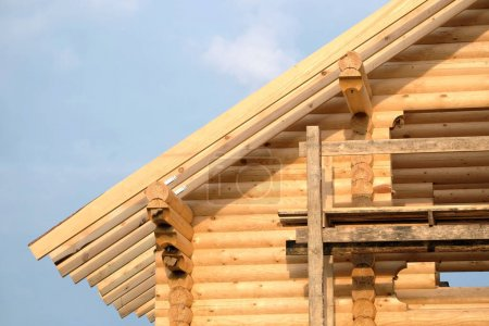 Process of wooden house straight roof slope mounting. Wooden country house construction