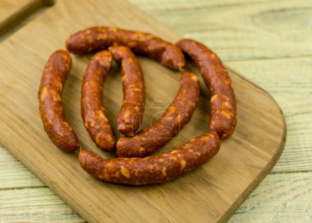 Smoked natural sausages   on a wooden surface....
