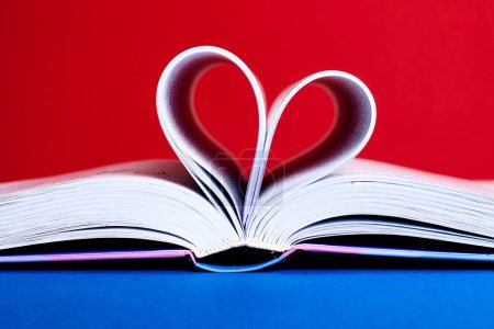 An open book with a folded heart of pages on a red...