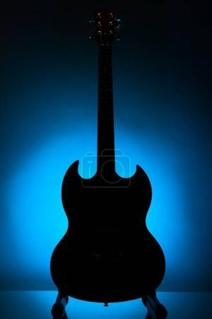 Photo pour Silhouette guitare électrique sur fond bleu - image libre de droit