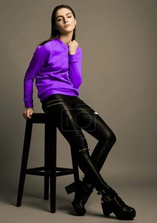 Photo pour Magnifique mannequin portant un pull violet foncé en studio. Assis sur une chaise - image libre de droit