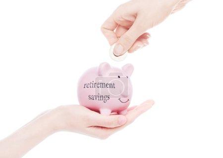 Foto de Mano femenina sostiene alcancía con ahorros para la jubilación mano texto de concepto poner moneda interior sobre fondo blanco - Imagen libre de derechos