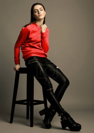 Photo for Beautiful fashion model with dark red jumper on grey background. Sitting on chair - Royalty Free Image