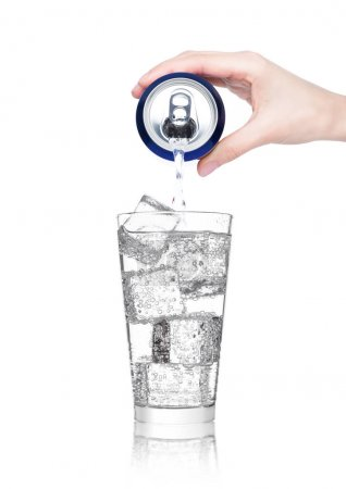 Photo for Female hand pouring sparkling mineral water from aluminium can to glass on white background - Royalty Free Image
