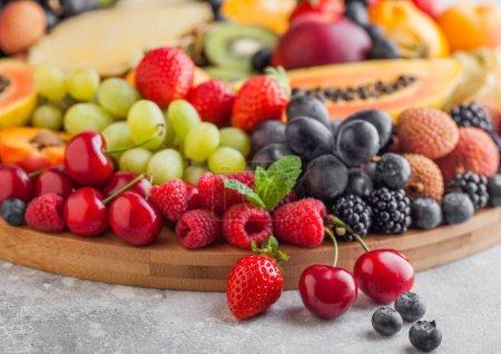 Photo pour Fruits exotiques et baies fraîches crues d'été biologiques dans un grand plateau rond sur fond de cuisine légère. Papaye, raisin, nectarine, orange, framboise, kiwi, fraise, litchi, cerise. Vue du dessus - image libre de droit