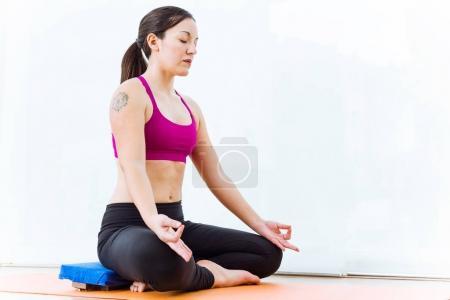 Photo pour Portrait de la belle jeune femme de pratiquer l'yoga à la maison dans la position du lotus. - image libre de droit