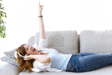Photo pour Portrait de belle jeune femme écoutant de la musique à la maison . - image libre de droit
