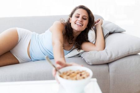Photo for Portrait of beautiful young woman eating cereals at home. - Royalty Free Image