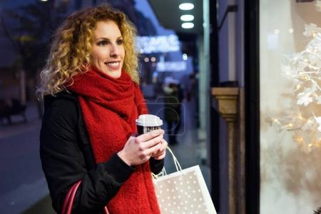 Beautiful young woman looking at the shop window at night.