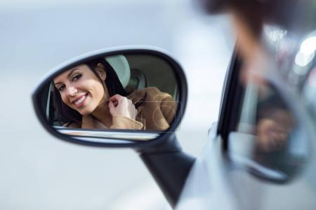 Beautiful young woman looking in the rearview mirror.