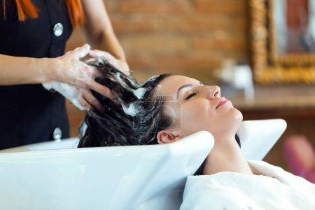 Photo pour Portrait de belle jeune femme lave les cheveux dans un salon de beauté . - image libre de droit