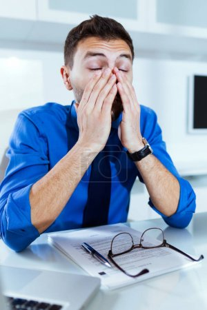 Handsome young businessman stressed while working with laptop in the office.