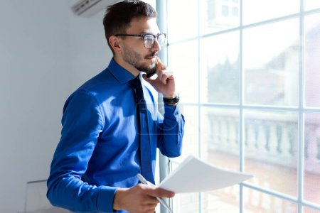 Photo for Portrait of handsome young businessman using his mobile phone in the office. - Royalty Free Image