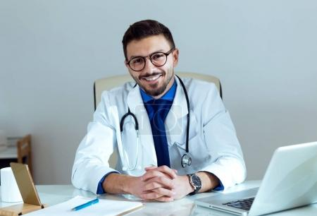 Confident male doctor smiling and looking at camera in the office.