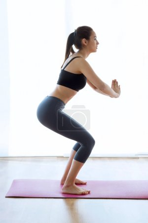 Photo for Portrait of sporty young woman doing hypopressive abs indoor. - Royalty Free Image