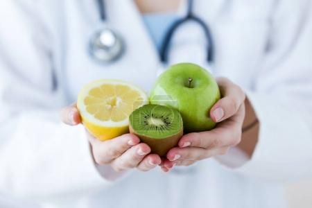 Doctor hands holding fruit such as apple, kiwi and lemon.