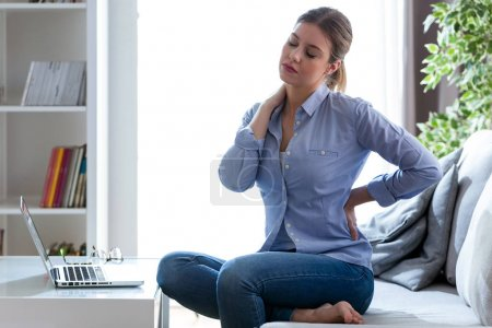 Tired young woman with shoulder and back pain sitting on the couch at home.