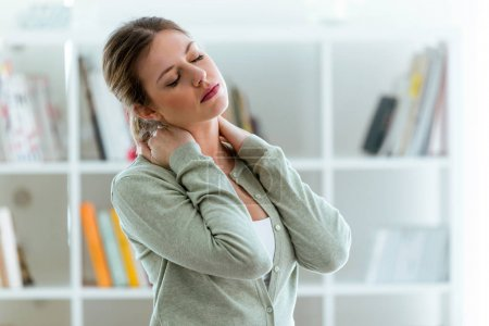 Tired young woman with neck pain at home.