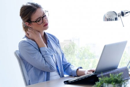 Tired young woman with neck pain using her laptop at home.
