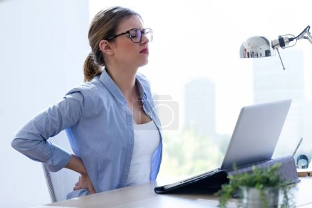 Tired young woman with back pain using her laptop at home.