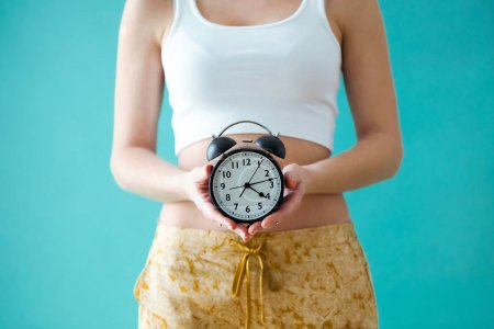 Young woman holding a clock over blue background.