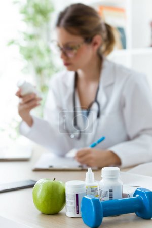 Female dietician holding a nutritional supplement while writing the properties in the consultation.