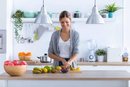Photo pour Tir de jolie jeune femme préparant une boisson aux fruits dans la cuisine à la maison. - image libre de droit