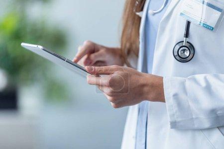 Photo pour Gros plan d'une femme médecin utilisant sa tablette numérique au bureau . - image libre de droit