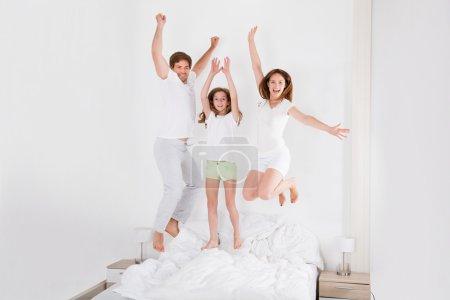 Photo pour Famille heureuse sautant sur le lit ensemble dans leur chambre - image libre de droit