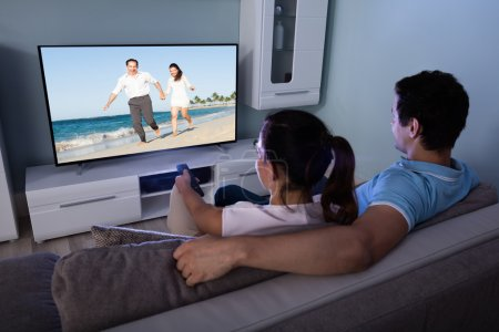 Photo for Rear View Of Couple Watching Movie On Television Together In Living Room - Royalty Free Image