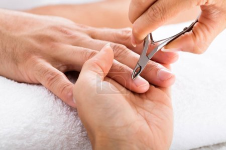 Photo pour Gros plan de manucure faisant le parage des ongles masculins dans le salon de beauté - image libre de droit