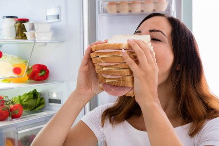 Woman eats in front of refrigerator
