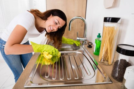 Female cleaning stainless steel sink