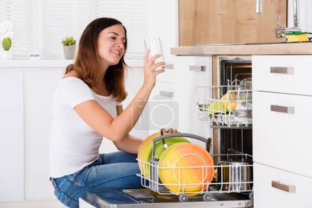Young woman  taking drinking glass from dishwasher...
