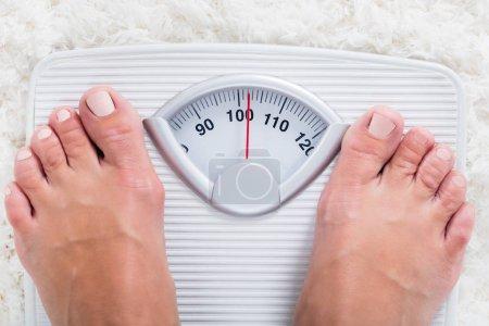 Photo pour Faible section de la personne obèse en surpoids mesurant le poids corporel sur l'échelle de pesée - image libre de droit
