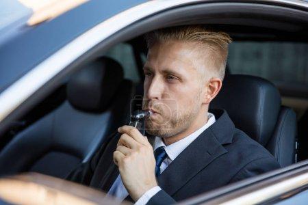 Photo pour Homme assis à l'intérieur de la voiture prenant test d'alcool - image libre de droit