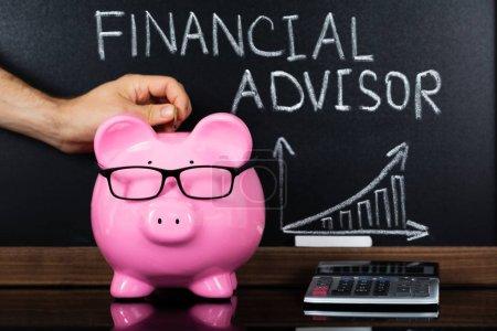 Photo pour Personne en insérant la pièce de monnaie dans une tirelire montrant le Concept de conseiller financier sur tableau noir - image libre de droit