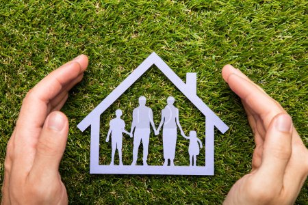 Photo for High Angle View Of Person Holding Protective Hands On Family Home At Grass - Royalty Free Image
